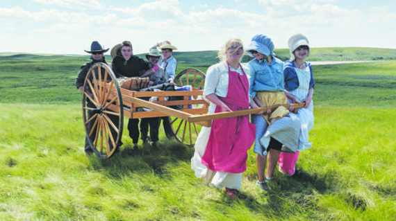 Youth pull handcarts across the prairie in pioneer re-enactment
